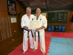 Shihan Howard Lipman presents Shihan Rick Cunningham his dojo operator license