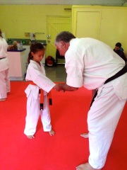 Sensei Mark McFadden assisting a Little Lion with their technique.