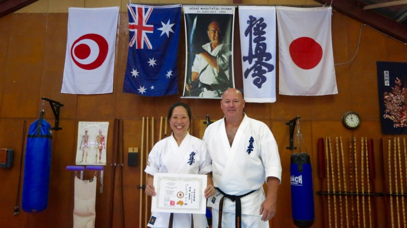 Trish Tan receives her 3rd Kyu in Kobudo from Shihan Rick Cunningham.