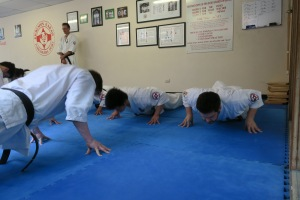 Sempai Jono demonstrates finger-tip push-ups for Shodan.