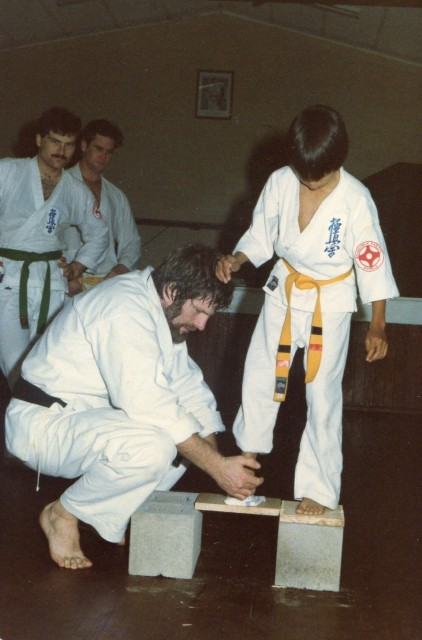 Shihan Howard teaches a young Sensei Mark Ting how to break a board