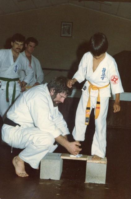 Shihan Howard teaches a young Sensei Mark Ting how to break a board